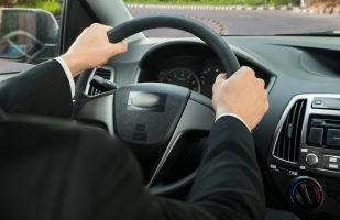 Close-up Of A Driver's Hand On Steering Wheel While Driving Car